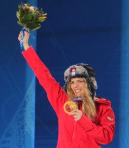 Bild bei der Siegerehrung in Sochi zeigt Snowboard Olympiasiegerin Patrizia Kummer mit Blumenstrauss und Goldmedadaille