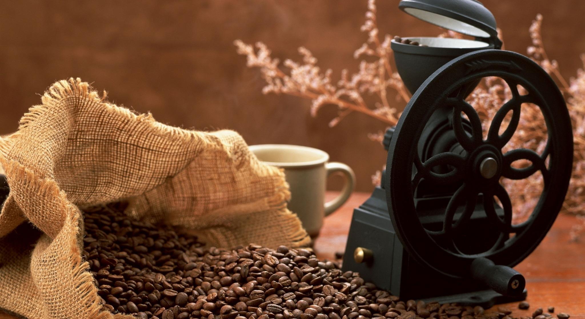 Ein offener Sack Kaffeebohnen mit einer alten handbetriebenen Kaffeemühle im Café Hängebrücke Goms