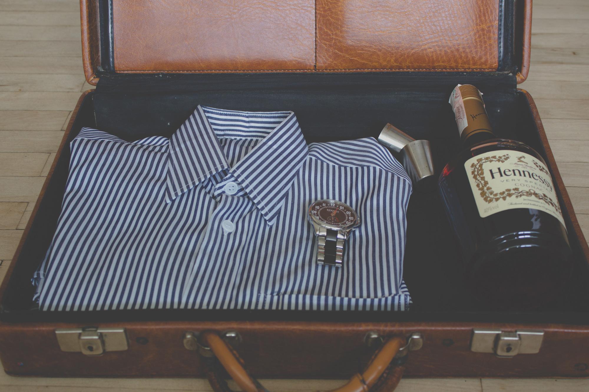 ein Lederkoffer mit Flasche Hennessy Cognac, Uhr und Hemd liegt auf dem Tisch in einer unserer Ferienwohnungen im Goms