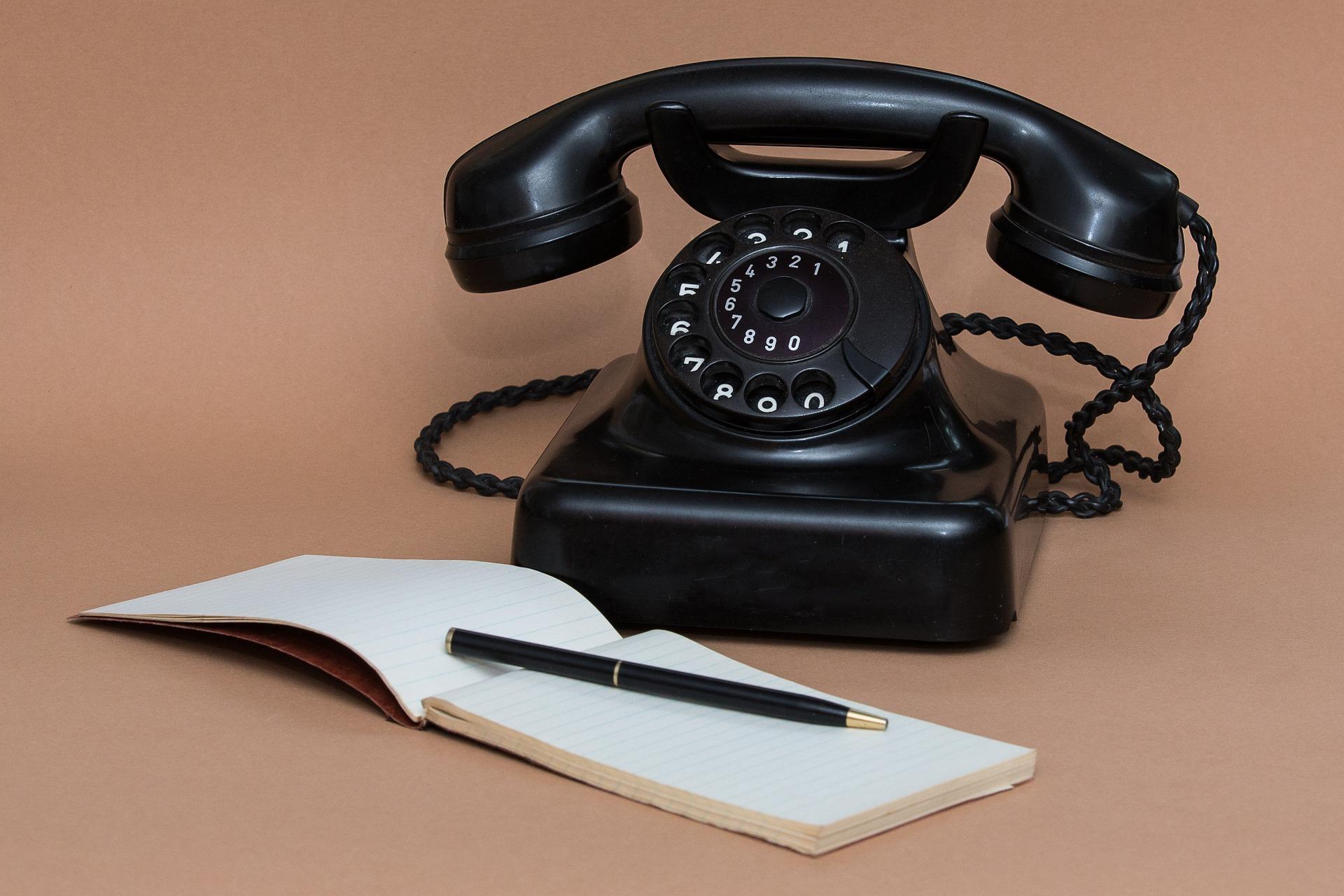 Ein altes Telefon mit Wählscheibe und ein Notizblock mit Stift sind Symbol für den Kontakt Hängebrücke
