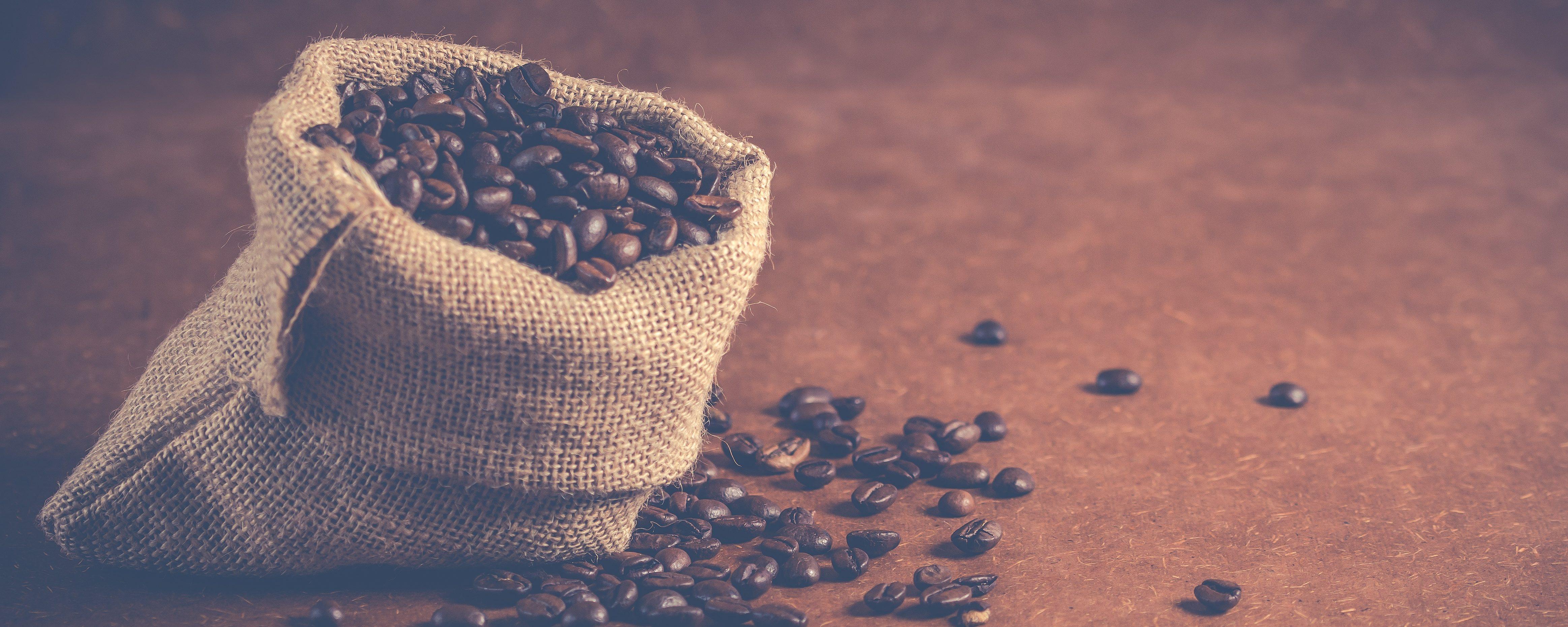 Ein kleines Säcklein mit gerösteten Kaffeebohnen steht offen auf einer braunen Unterlage.