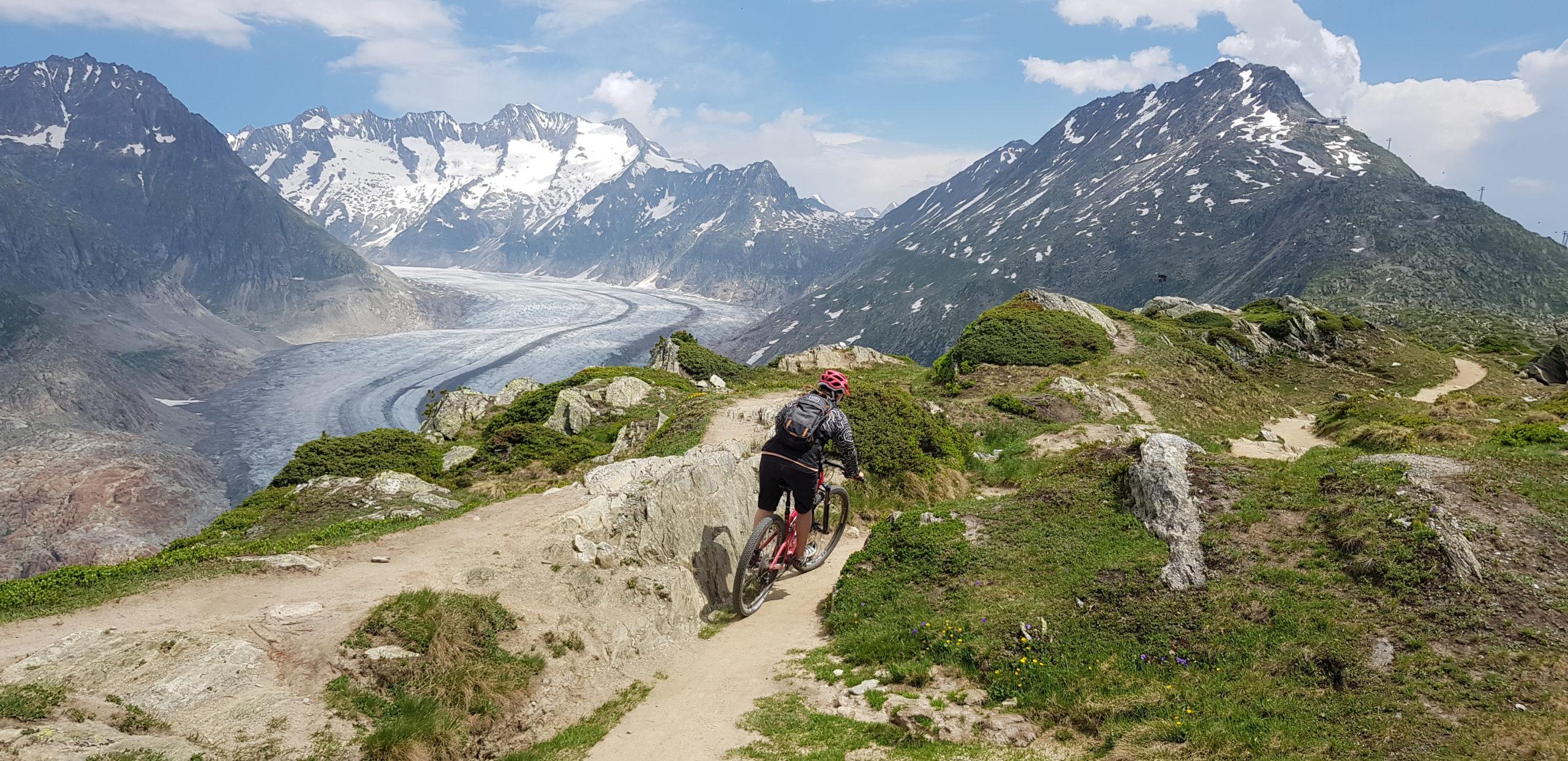 Patrizia Kummer bikt den Trail des Stoneman Glaciara. Im Hintergrund ist der majestätische Aletsch Gletscher als Kulisse einfach beeindruckend.