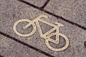 Ein Fahrraddzeichen schmückt einen Pflasterstein und markiert so einen Fahrradweg.
