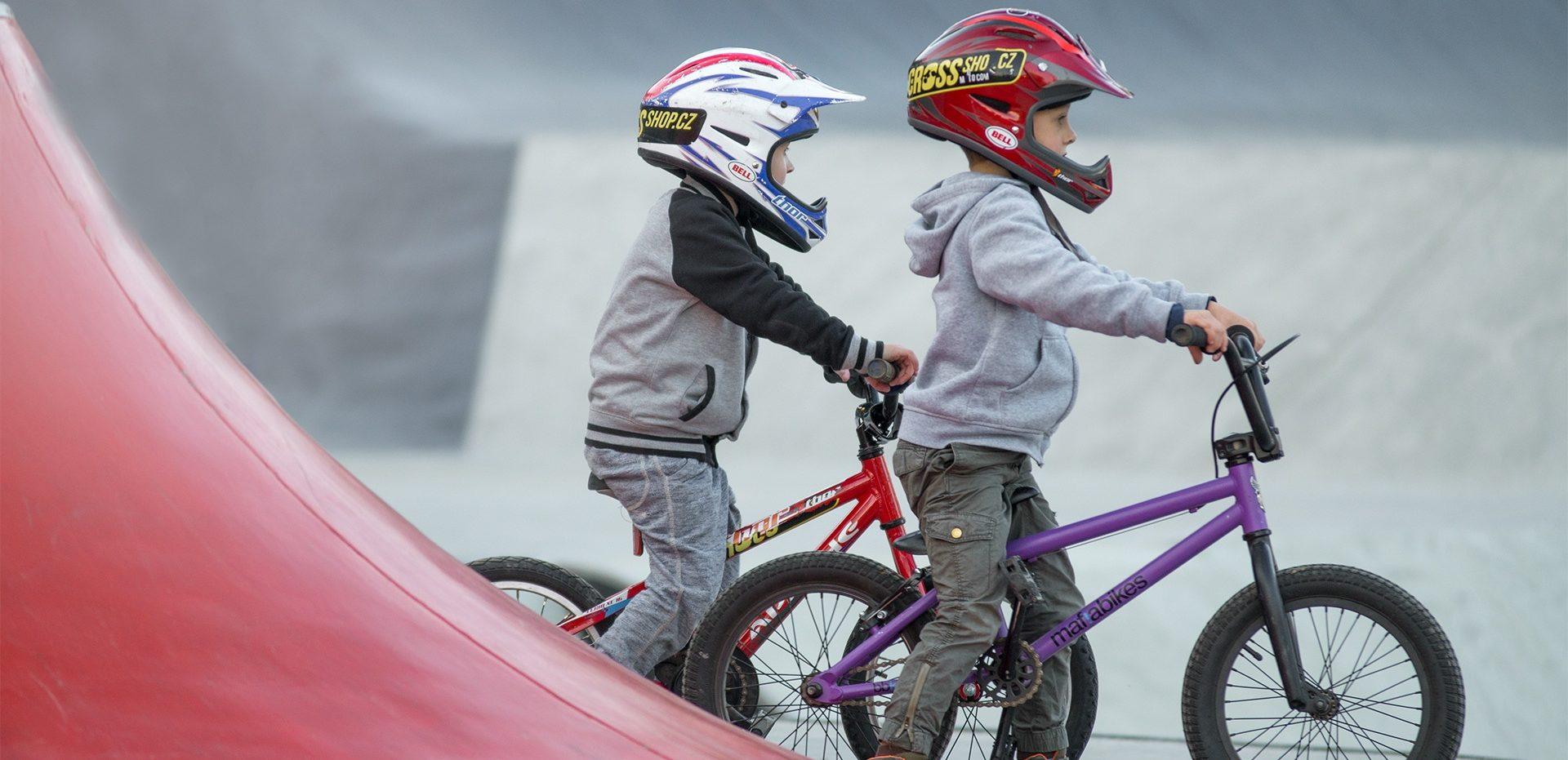 Zwei Kinder fahren mit ihren kleinen Bikes auf dem Pump Track in Bellwald.
